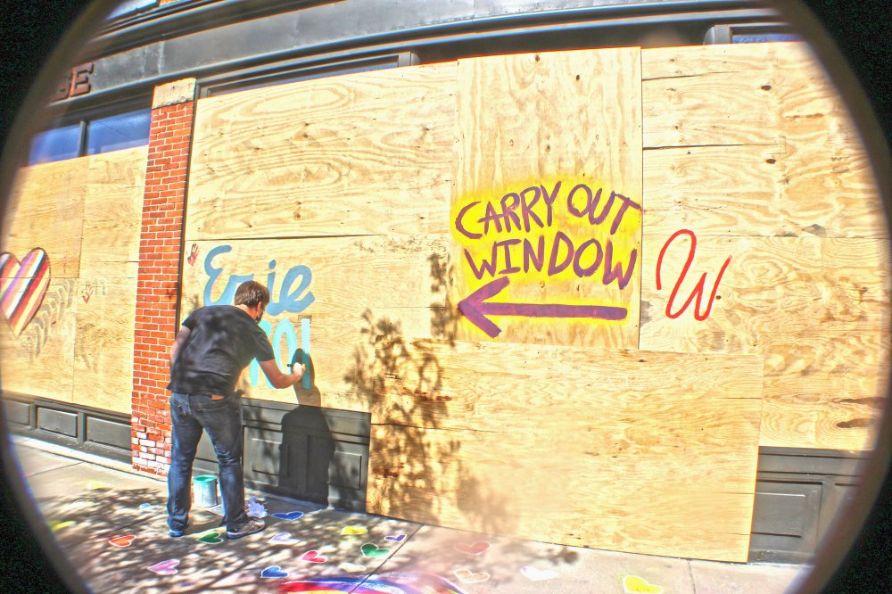 <p>Zach Flock paints temporarily boarded up windows. Photo by Nick Warren.</p>