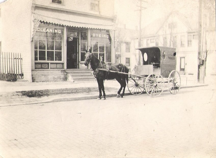 """<p><span style=""""color: #3c4043; font-family: Roboto, sans-serif; font-size: 16px; white-space: pre-wrap;"""">The Lawrence Cleaning and Dyeing business situated on the north west corner of West Third and Chestnut, with horse and company buggy on brick paved streets.This photo was likely taken in the early 1900s.</span></p>"""
