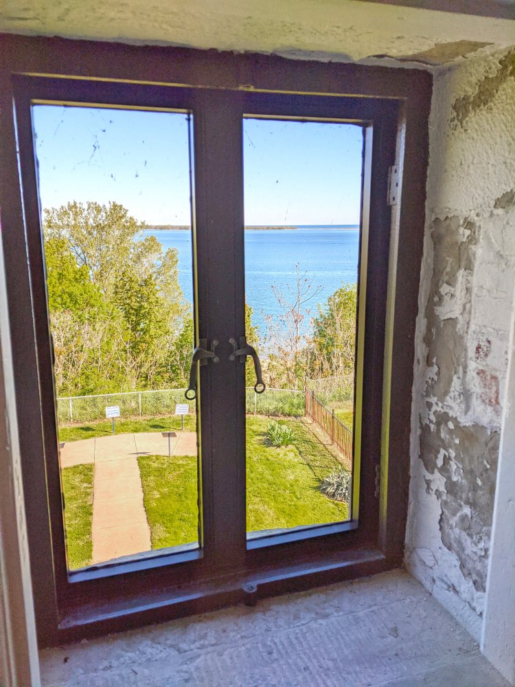 """<p><span style=""""color: #3c4043; font-family: Roboto, Arial, sans-serif; font-size: 16px; letter-spacing: 0.1px; white-space: pre-wrap;"""">A view of the channel between Lake Erie and the Bay through the window about halfway up the Land Lighthouse. This channel caused a lot of grief for early seafarers bringing goods into Erie, so a lighthouse was commissioned in 1818 to help guide boats more safely into Erie's harbor.</span></p>"""